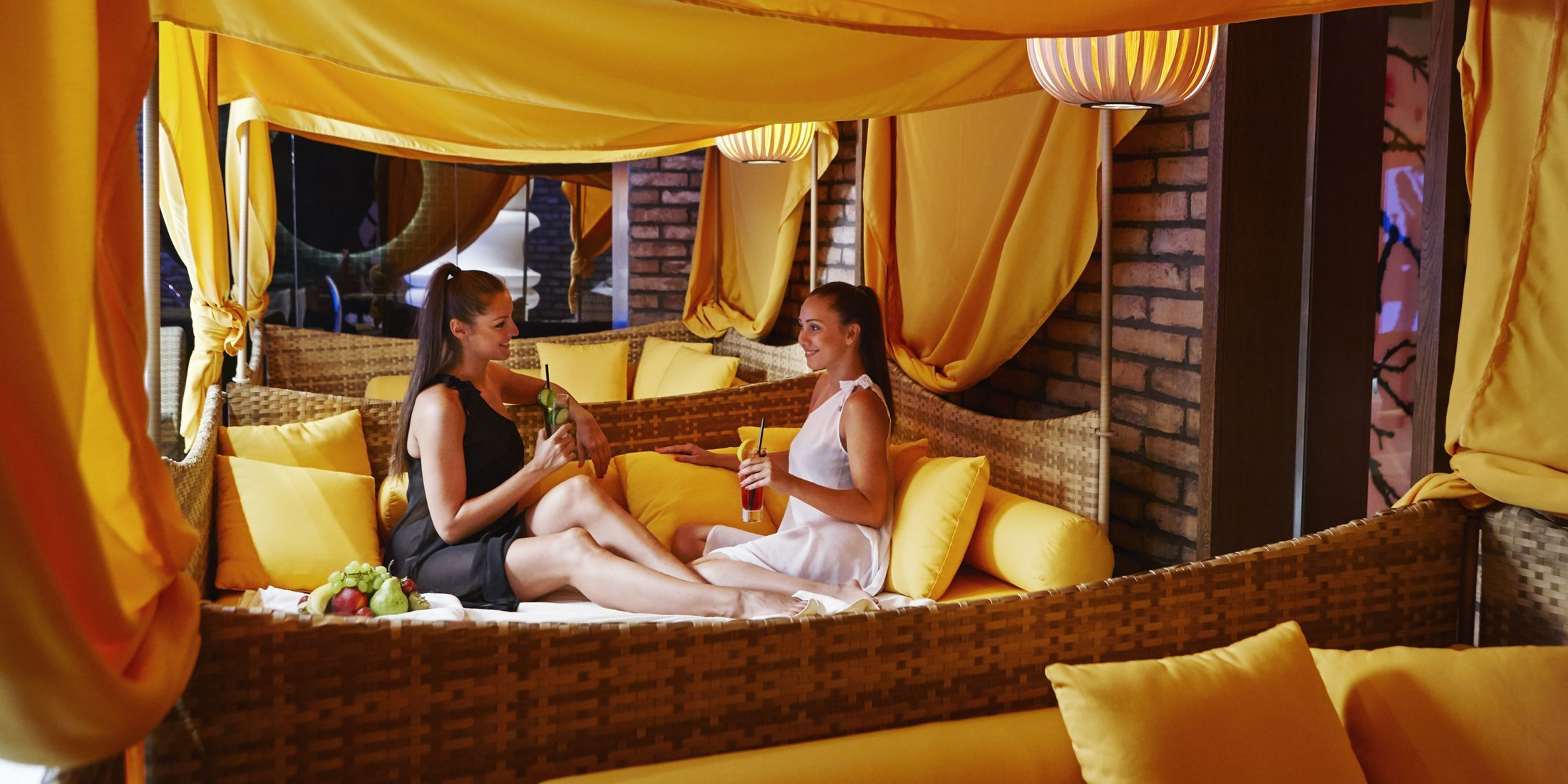 There are many yellow canopies poolside for guests to lounge in.